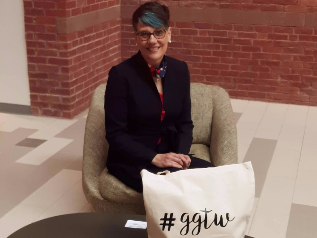 Tricia Yacovone-Biagi seated at a table with the GGTW swag bag.