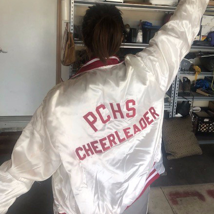 Woman wearing jacket that reads PCHS CHEERLEADER